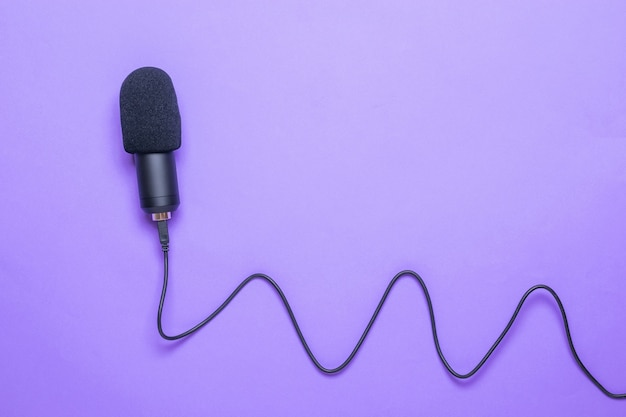 Modern microphone with a long cord on a purple surface