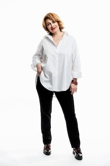 A modern middle-aged woman with red hair in a white shirt and black trousers.