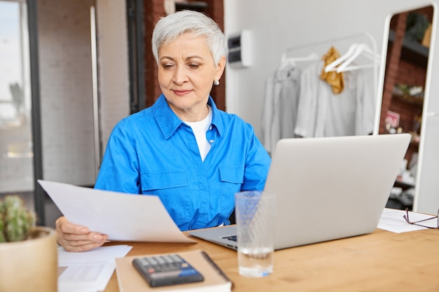 Modern middle aged woman with stylish short hair reading piece of paper in her hand working remotely on generic laptop pc, sitting at desk with calculator and copybook in cozy home interior