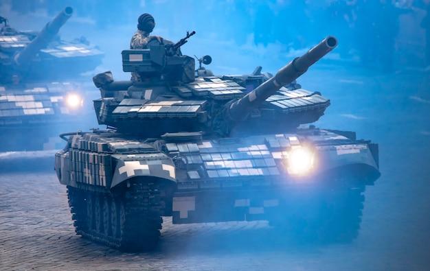 현대 군용 탱크. 도시의 연기가 자욱한 거리에서 기관총 뒤에 군인과 함께 헤드라이트를 켜고 움직입니다.