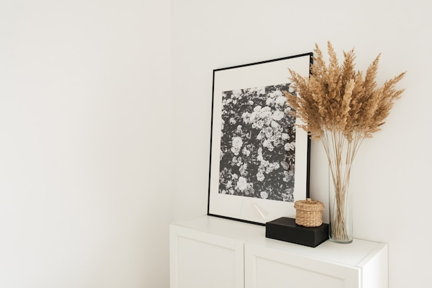 Modern minimal scandinavian nordic interior design. chest of drawers, photo frames, palm and decorations