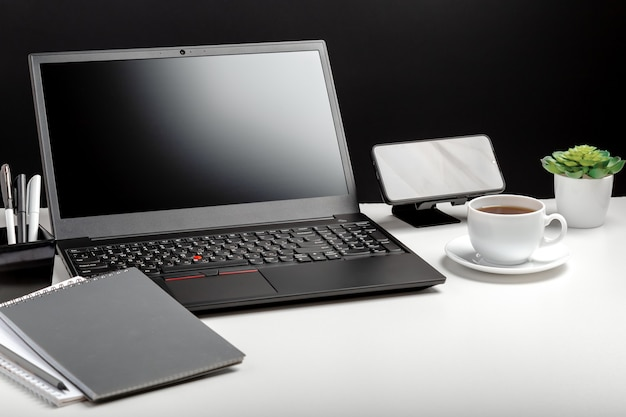 Modern minimal workplace for man. home office laptop screen blank display workspace. desktop with laptop pc smart phone, office suppliers, coffee cup plant flower. long web banner.