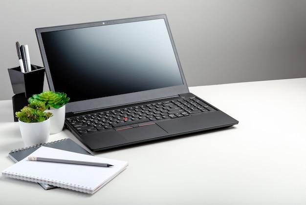 Современное минимальное рабочее место с копией пространства черный ноутбук, белый стол, серый фон. рабочее пространство пустого дисплея экрана компьтер-книжки домашнего офиса. настольный компьютер с офисными поставщиками портативных пк, цветок завода.