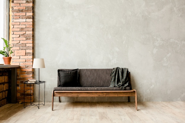 Modern minimalist interior with a sofa on an empty wall in the living room, mock up wall in living room room, loft style
