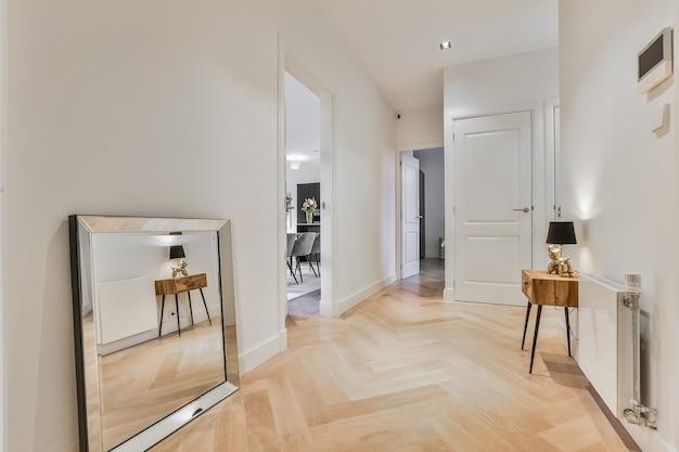 Современный минималистичный дизайн интерьера коридора в светлой квартире с дверями, ведущими в комнаты, и зеркалом в раме на паркетном полу у белой стены.