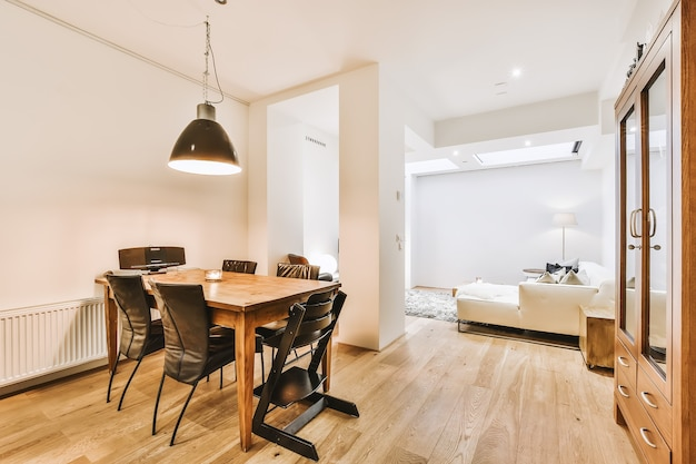 Современный минималистичный дизайн интерьера однокомнатной квартиры с открытой белой кухней и обеденной зоной со столом и стульями, освещенной лампой в стиле лофт.
