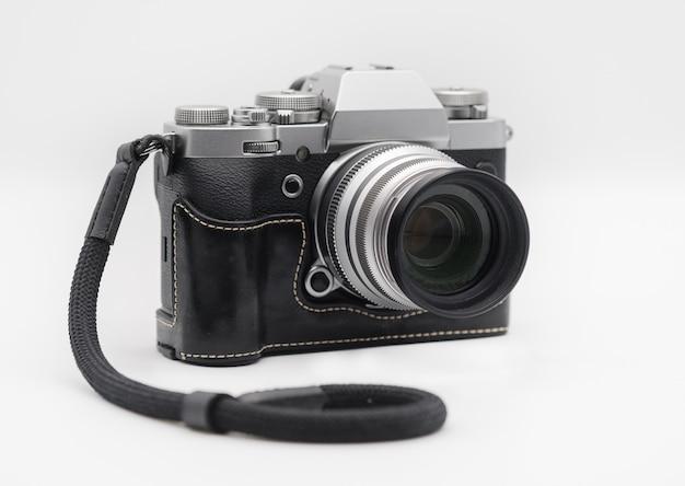 Современный беззеркальный фотоаппарат в кожаном полуприкрытии и коротком шнурке