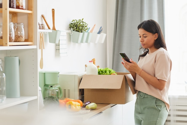 Modern mixed-race woman holding smartphone while standing by box of food in kitchen, mood delivery service and mobile app concept