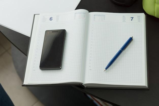 Современный мобильный телефон и синяя ручка на чистой записной книжке на черном столе.