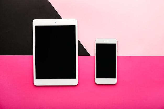 ピンクの現代の携帯電話とタブレット コンピューター