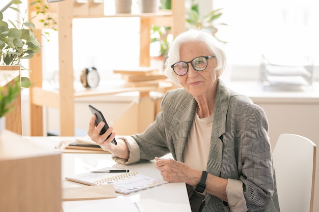 Modern and mobile senior female in formalwear and eyeglasses sitting by workplace in office