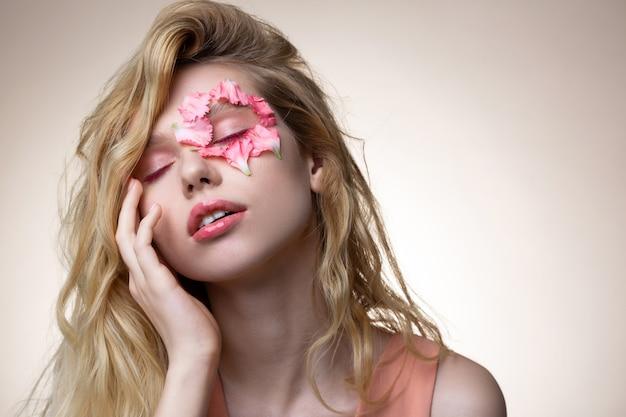 モダンモデル。顔に花びらを持つ現代の雑誌のポーズをとる優しい若いブロンドの髪のモデル