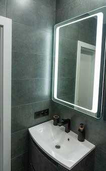 Современная монохромная серая ванная комната с белой керамической угловой раковиной или умывальником под большим зеркалом в рамке