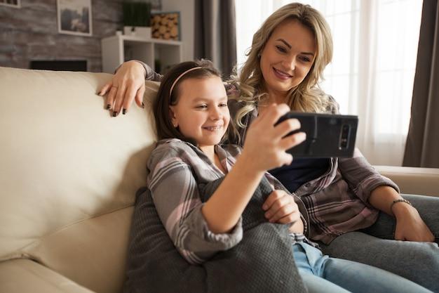 ソファに座ってスマートフォンで愛のビデオを見ている現代の母親と彼女の小さな娘。
