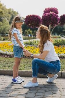 현대 어머니. 그녀의 귀여운 딸과 이야기하면서 잊을 수없는 느낌을주는 현대적이고 세련된 어머니