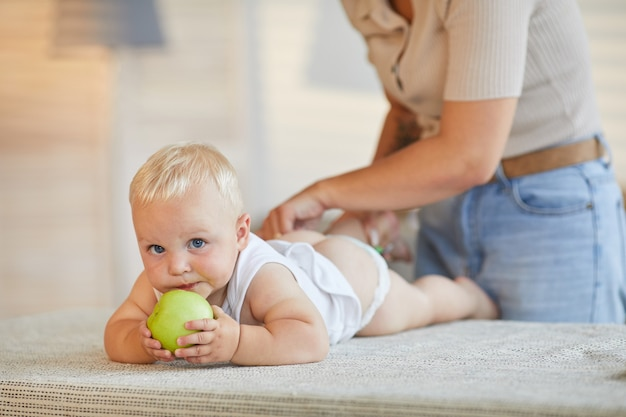 Modern mother changing clothes of her little baby son while he is biting green apple