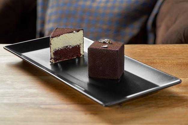 チョコレートのベロアで覆われたモダンなムースケーキ。テーブルの上のデザートフランス料理、レストランでお召し上がりいただけます Premium写真