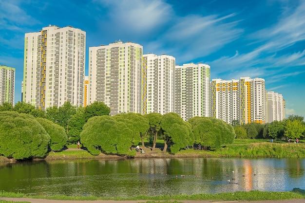 Современные разноцветные многоэтажные жилые дома у озера с зелеными деревьями в россии