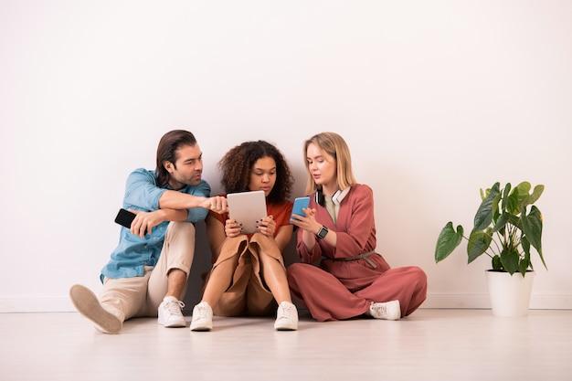 鉢植えの植物と床に座って、ガジェットに関する情報を互いに共有している現代の多民族の友人