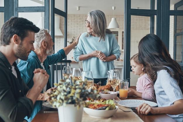 Современная многопоколенная семья общается и улыбается во время совместного ужина