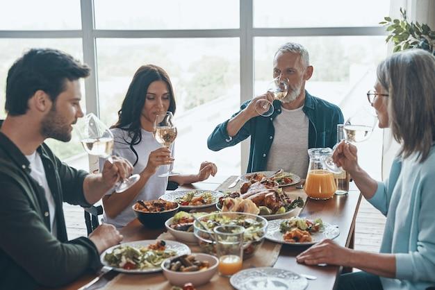 Modern multigeneration family drinking wine while having dinner together