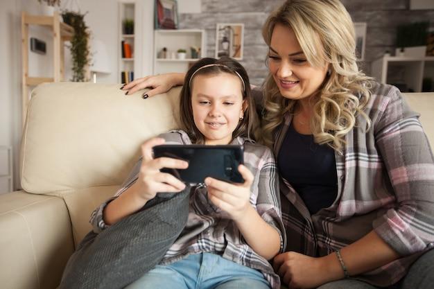 スマートフォンアプリケーションを使用してリビングルームのソファに座っている現代のお母さんと幸せな少女。