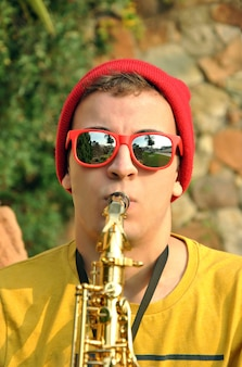 Modern musician posing with his saxophone in the garden