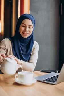 현대 무슬림 여성이 차를 마시고 카페에서 컴퓨터에서 작업
