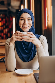 Modern muslim woman drinking tea and working on computer in a cafe