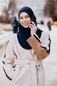 Donna musulmana moderna che parla al telefono
