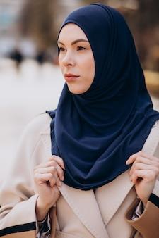 거리에서 걷는 headscarf를 입고 현대 무슬림 여성