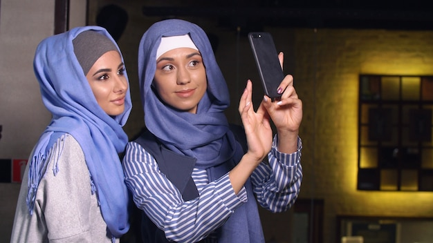 Modern muslim women take pictures on a mobile phone. girls in hijabs talking and smiling.