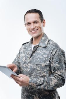 최신 탐색. 현대 탐색 도구를 사용하는 동안 웃고 태블릿을 들고 즐거운 긍정적 인 군인