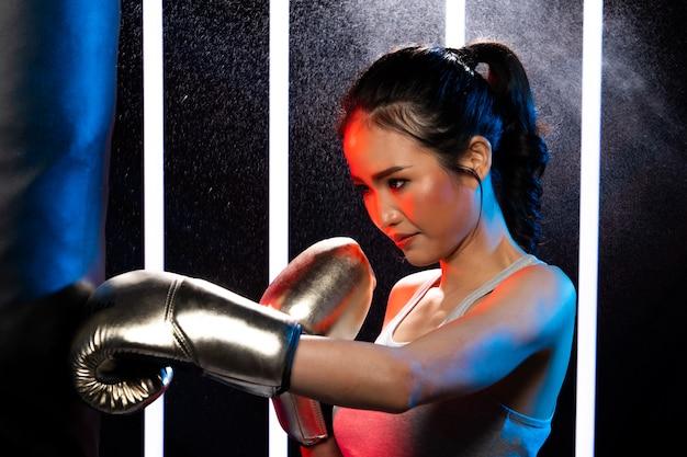 Девушка упражнений в modern neon boxing gym сильно