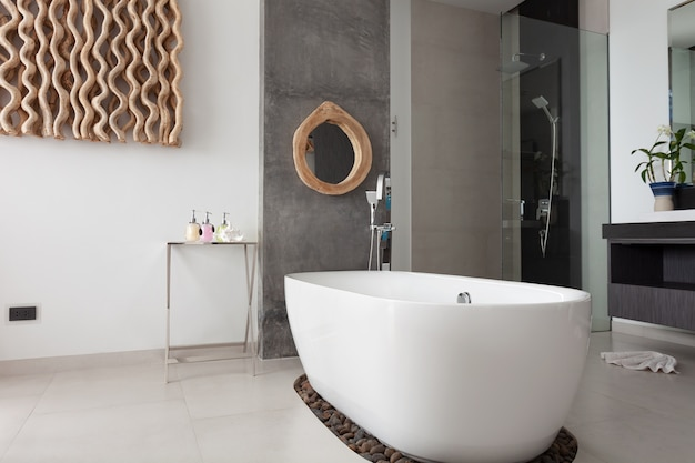 新しいヴィラまたはホテルのモダンな建物に白い石のバスタブ付きのモダンな新しいバスルームのインテリアデザイン。