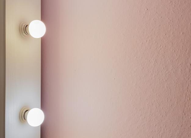 化粧とフルレングスのショッピングのための大きなフロアミラーからの2つの電球を備えたモダンな新しいフラットピンクの壁。抽象的なモダンなトレンディなテクスチャの背景。テキスト用のスペースをコピーします。