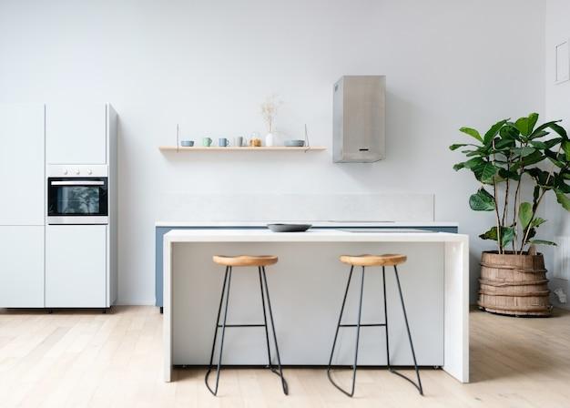 白い家具とダイニングテーブルを備えたキッチンのモダンで新しい明るいインテリア。