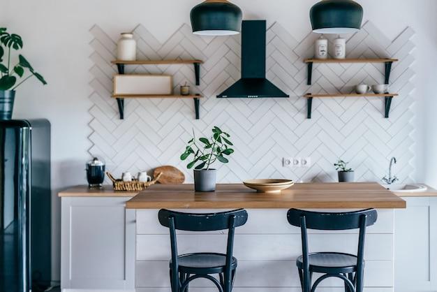 白い家具とダイニングテーブル付きのキッチンのモダンな新しい明るいインテリア。