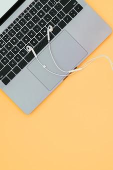 Современный красивый блокнот и белые наушники на оранжевой поверхности