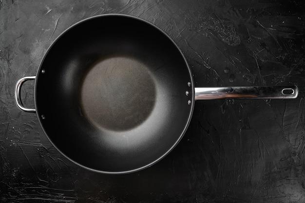 Современная сковорода с антипригарным покрытием, сковорода или кастрюля с копией пространства для текста или еды с копией пространства для текста или еды, плоский вид сверху, на черном фоне темного каменного стола