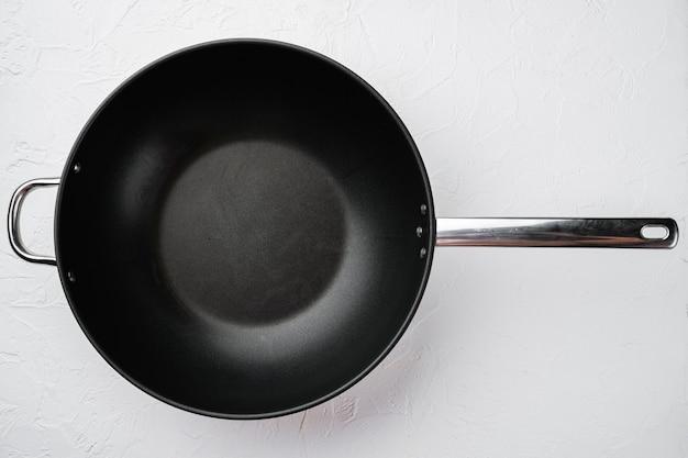 Современная сковорода с антипригарным покрытием, сковорода или кастрюля с копией пространства для текста или еды с копией пространства для текста или еды, плоская планировка, вид сверху, на фоне белого каменного стола