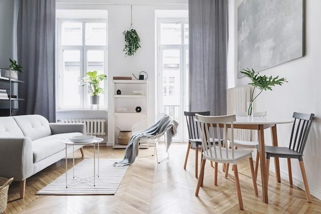 우아한 가정 장식의 디자인 회색 소파, 커피 테이블, 식물, 세련된 액세서리, 장식, 카펫 및 책꽂이가있는 현대 북유럽 거실 인테리어