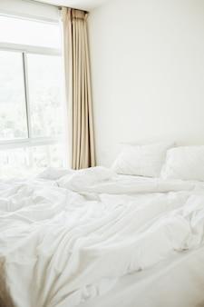 현대 북유럽 스칸디나비아 인테리어 디자인 컨셉. 침대, 흰색 담요, 베개 및 베이지 색 커튼이있는 아름다운 이국적인 전망의 침실