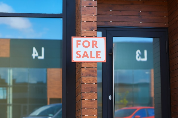 Modern office building with placard for sale hanging on the brick wall