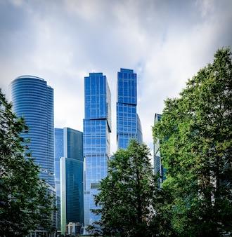 Современные офисные здания и зеленые деревья городского парка