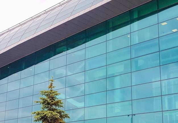 ガラスとコンクリートで作られたモダンなオフィス商業ビル、外観、建物の背景にトウヒ。