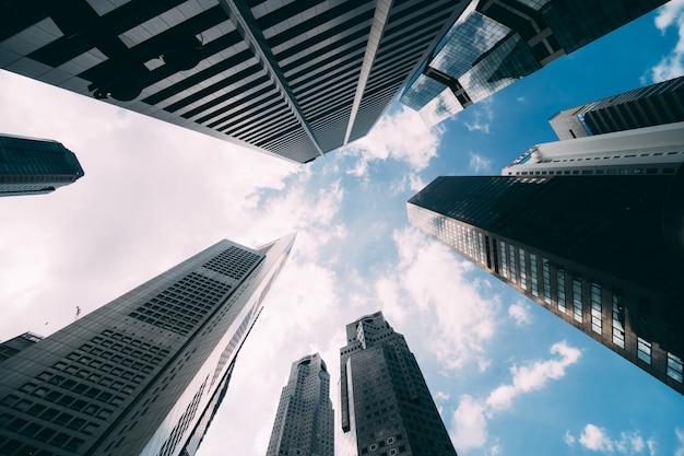 Современное офисное корпоративное здание. взгляд низкого угла небоскребов в городе сингапура. панорамный и перспективный взгляд концепция дела архитектуры техника индустрии успеха.