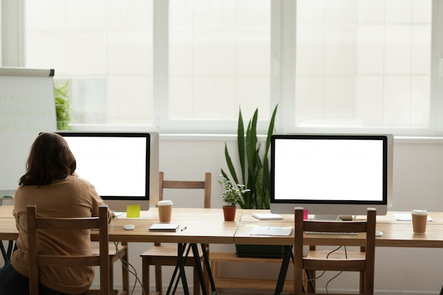Modern office coworking space with woman working alone on computer