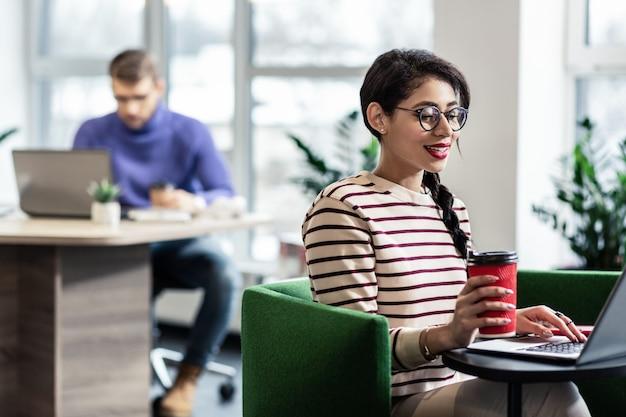 Современный офис. довольная женщина, выражающая позитив, находясь на своем рабочем месте