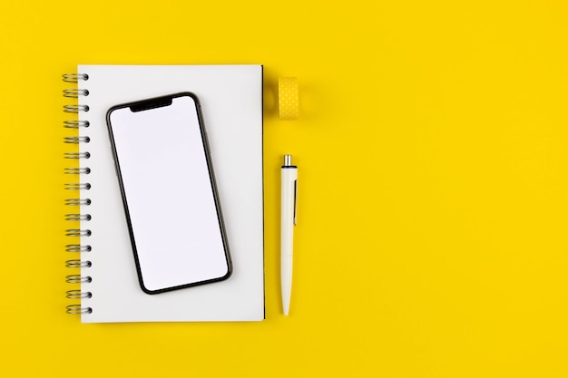 Плоский современный офисный стол с макетом экрана смартфона, спиральным бумажным блокнотом и ручкой на желтой поверхности